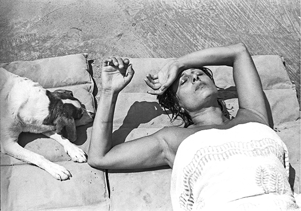 Paolo Di Paolo, Anna Magnani at her villa in San Felice Circeo, Rome, 1955. Beautiful woman lying in the sun with a dog next to her.